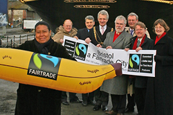Photograph of a lady holding a giant fairtrade banana with Bristol council members in the background